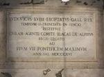 Tulisan di bagian bawah tugu di depan  Trinità dei Monti